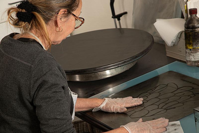Elisabeth Mathisen setter inn kobberplaten med trykksverte. (Foto: Mats Linder)