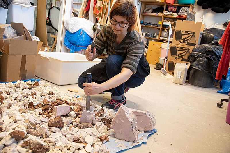 Lina Meseke hamrer løs på gammel størknet leire som skal gjenbrukes i et nytt prosjekt. (Foto: Mats Linder)