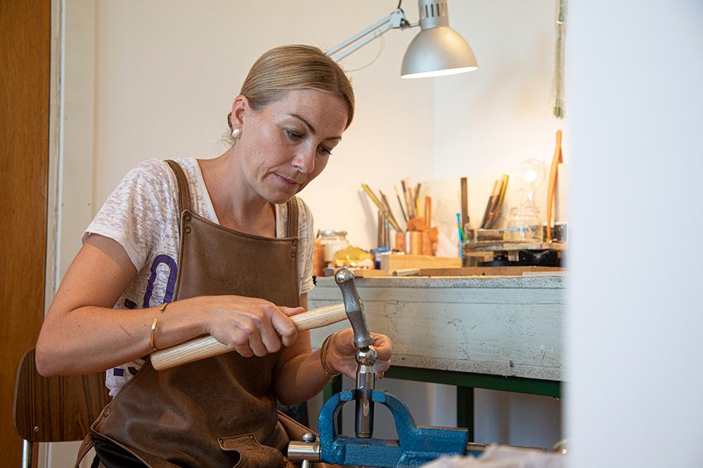 Hedvig Sommerfeldt har festet et knoppstempel til skrustikken som metallet formes etter, alt etter hammeren slår opp formen. (Foto: Mats Linder)