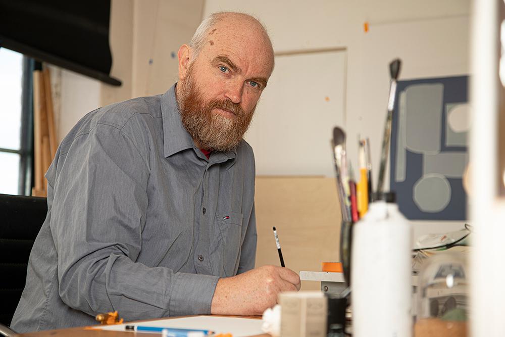 Arne Revheim sitter og maler på et lite bilde. (Foto: Mats Linder)