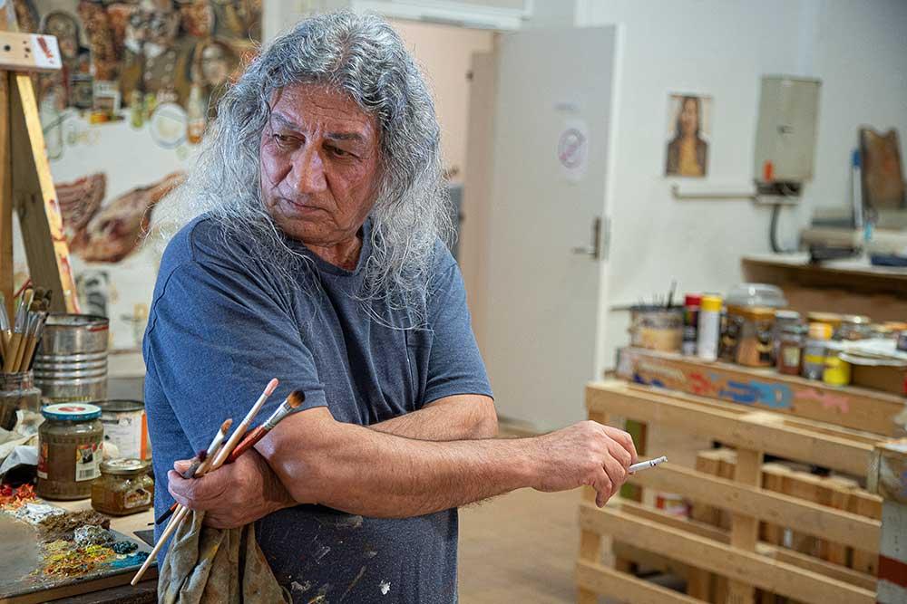 For å få en pause fra maleriet tar Davood seg en røyk. (Foto: Mats Linder)